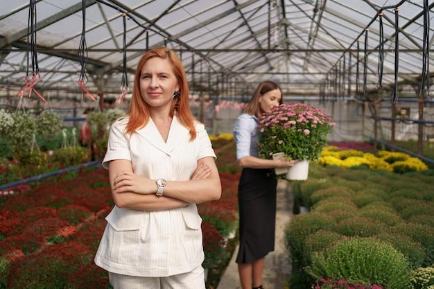 たくさんの花を持っている腕を組んでポーズをとっている温室の所有者とガラスの屋根の下にピンクの菊のポットを持っている同僚の笑顔 無料写真