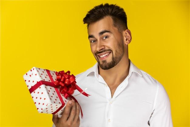 Ragazzo sorridente che tiene un contenitore di regalo Foto Gratuite