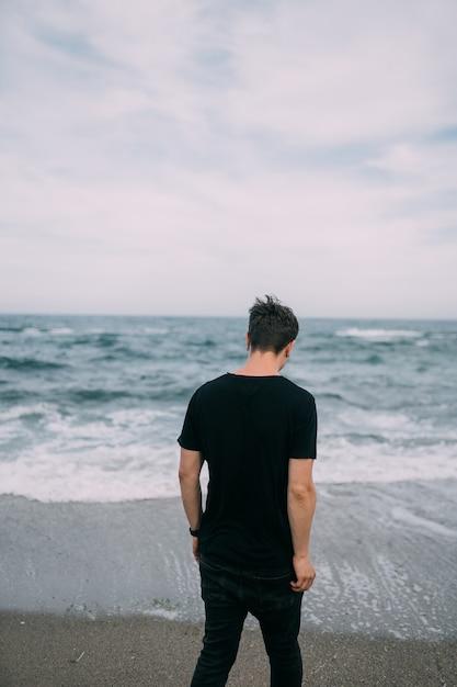砂浜の海岸に立っている笑顔の黒いtシャツの男。 無料写真