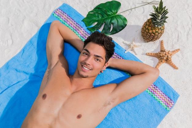 Smiling guy sunbathing on beach Free Photo
