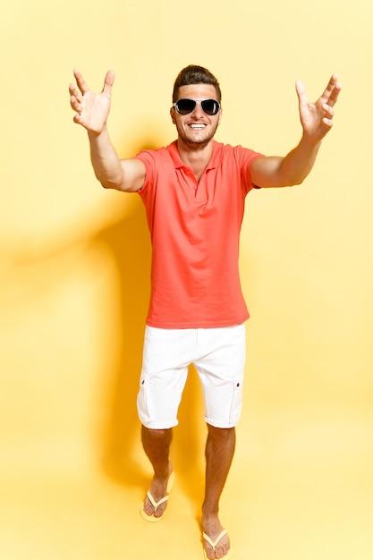 Smiling guy in sunglasses stepping towards camera Premium Photo
