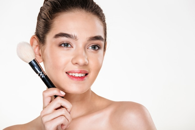 Smiling half-naked woman with fresh skin holding brush for makeup close to face and looking aside Free Photo