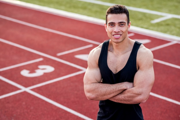Smiling handsome athlete in a sporty outfit with his arms crossed on race track looking at camera Free Photo