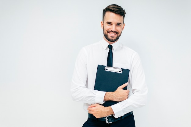 Smiling handsome business guy with folder Free Photo