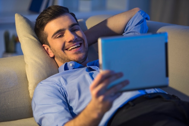 Smiling handsome man is using digital tablet at home. Premium Photo