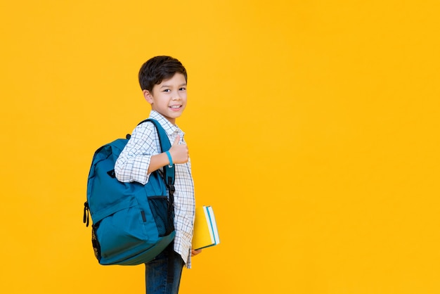 Smiling handsome mixed race schoolboy with books and backpack giving thumbs up isolated on yellow wall with copy space Premium Photo