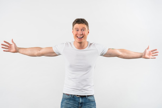Smiling handsome young man outstretching her arms isolated on white background Free Photo