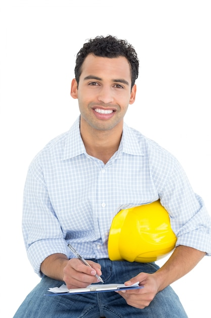 Smiling handyman with yellow hard hat writing in clipboard Premium Photo