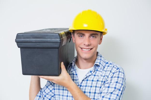 Smiling handyman in yellow hard hat carrying toolbox Premium Photo
