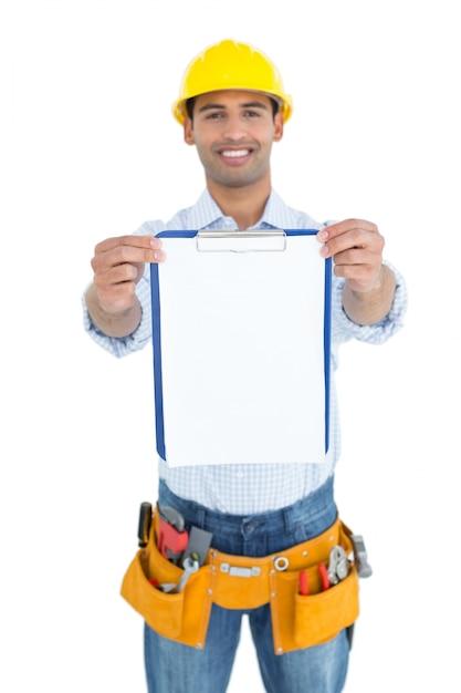 Smiling handyman in yellow hard hat holding clipboard Premium Photo