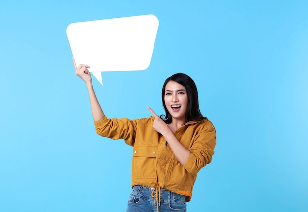 Smiling happy asian woman holding blank speech bubble and with empty space for text on blue background. Free Photo