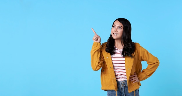 Smiling happy asian woman with her finger pointing isolated on light blue banner background with copy space. Free Photo