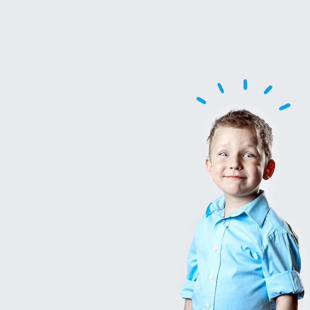 A smiling happy boy in blue shirt on light background Premium Photo