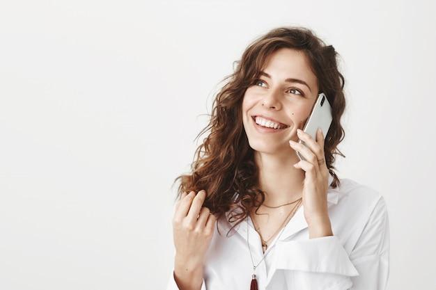 Улыбается счастливая деловая женщина разговаривает по телефону и смотрит в левый верхний угол Бесплатные Фотографии