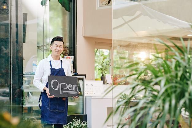 폐쇄가 끝난 후 고객을 맞이할 때 입구에 서서 열린 사인을 보여주는 웃는 행복한 카페 웨이터 프리미엄 사진