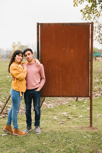 Smiling happy couple in denim in countryside next to metal rusty stand Free Photo