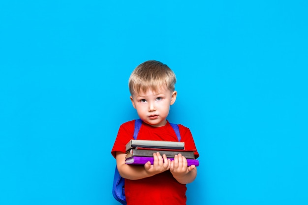 a91265c47454 Smiling happy cute clever boy with backpack. child with a pile of ...
