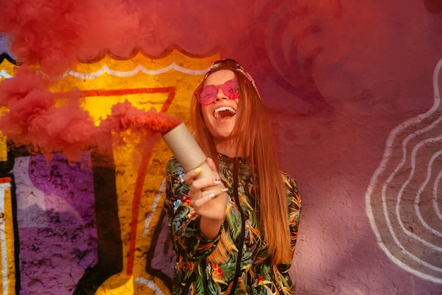 Smiling happy girl in sunglasses with red smoke bomb, standing near the wall with graffiti. Free Photo
