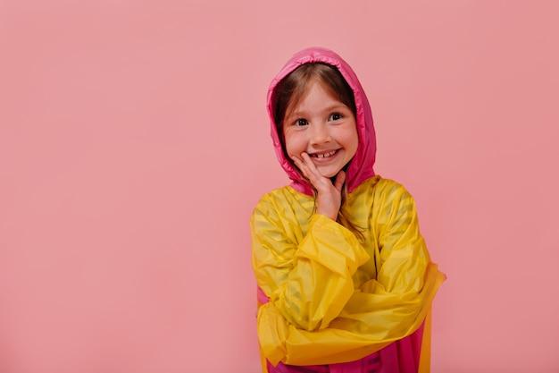 Улыбающаяся счастливая девушка в ярком плаще улыбается и держит руку возле лица Бесплатные Фотографии