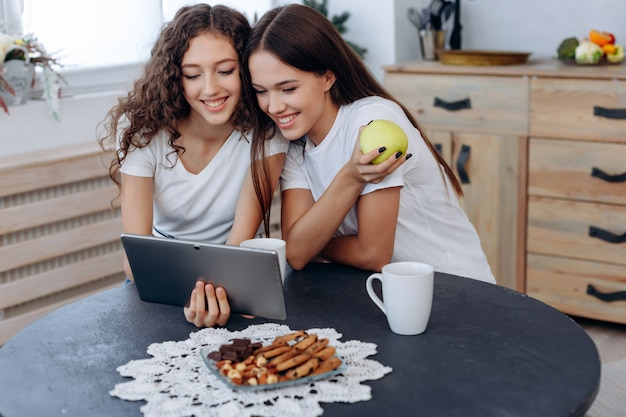 タブレットで面白いビデオを見ている幸せな女の子の笑顔、彼女の手でリンゴを保持している女の子の1つ Premium写真