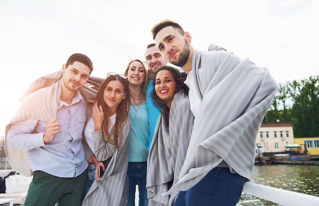 Sorridendo felice gruppo di amici all'aperto sul molo della spiaggia. Foto Gratuite