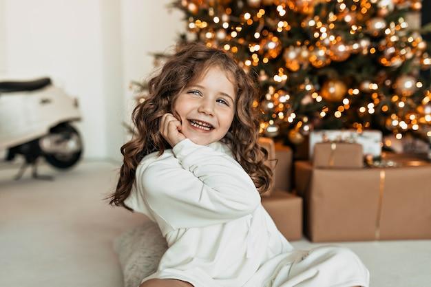 크리스마스 트리에 앉아있는 동안 행복한 미소로 포즈를 취하는 흰색 니트 스웨터를 입고 곱슬 머리를 가진 행복 한 어린 소녀 미소 무료 사진