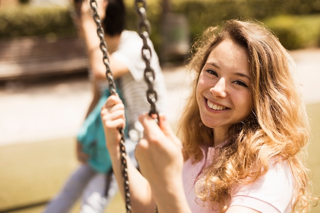 Smiling happy schoolgirl sitting on swings Free Photo