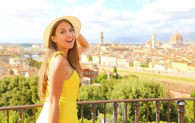 Улыбается счастливая туристическая девушка во флоренции, италия. портрет молодой женщины, посещающей красоту тосканы в италии. Premium Фотографии