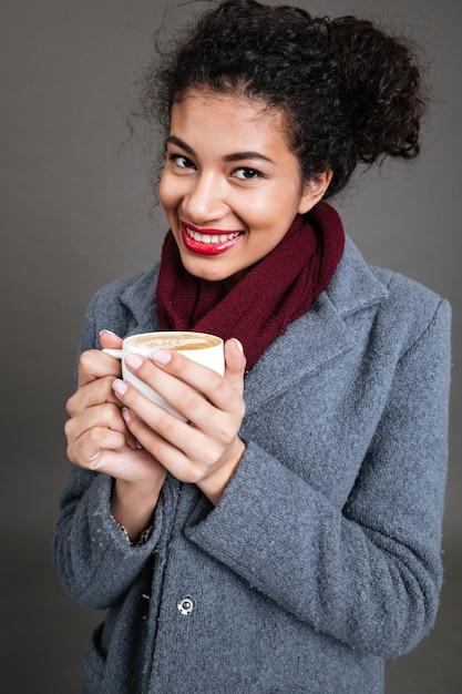 Улыбается счастливая женщина в пальто, держа чашку кофе Бесплатные Фотографии
