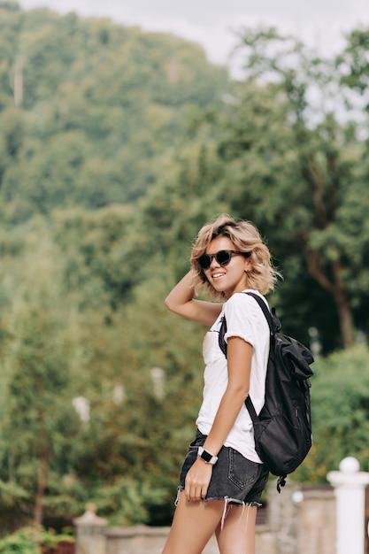 Donna felice sorridente con t-shirt bianca vestita di acconciatura corta e pantaloncini in occhiali da sole neri che viaggiano in montagna, buona giornata di sole, escursioni in montagna Foto Gratuite