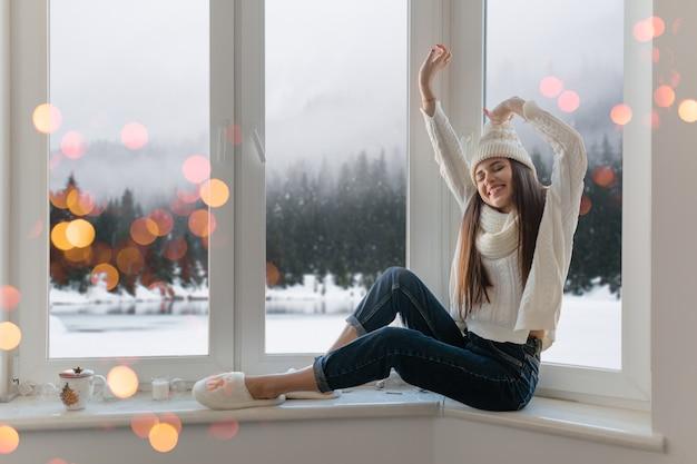 세련 된 흰색 니트 스웨터, 스카프와 모자 크리스마스에 창턱에 집에 앉아 웃 고 행복 한 젊은 매력적인 여자 손을 잡고 재미, 겨울 숲 배경보기, 조명 Bokeh 무료 사진