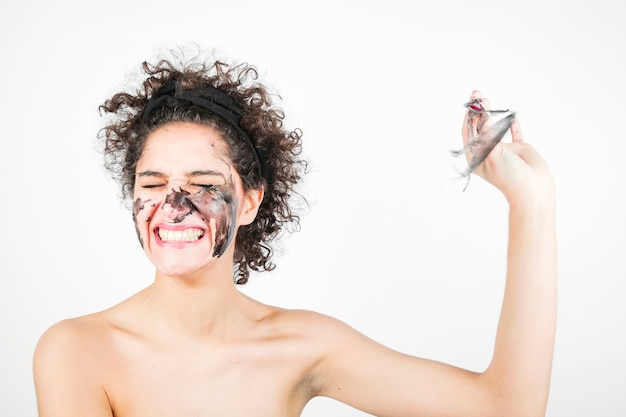 Smiling happy young woman removing facial mask against white background Free Photo