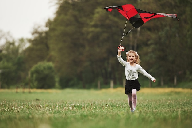 Smiling and having fun. happy girl in casual clothes running with kite in the field. beautiful nature Premium Photo
