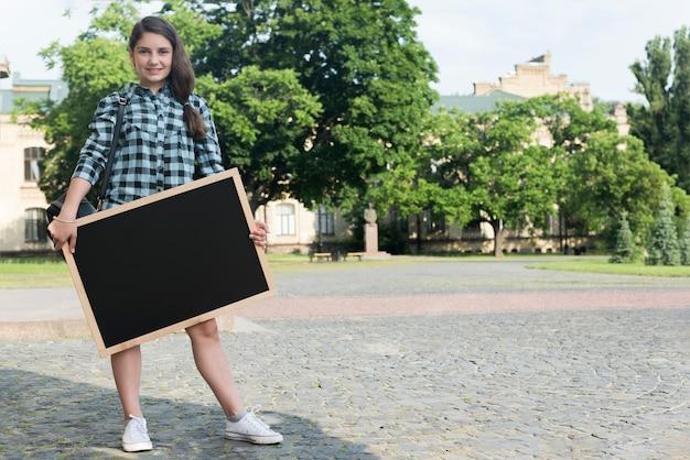 Smiling highschool girl holding blackboard Free Photo