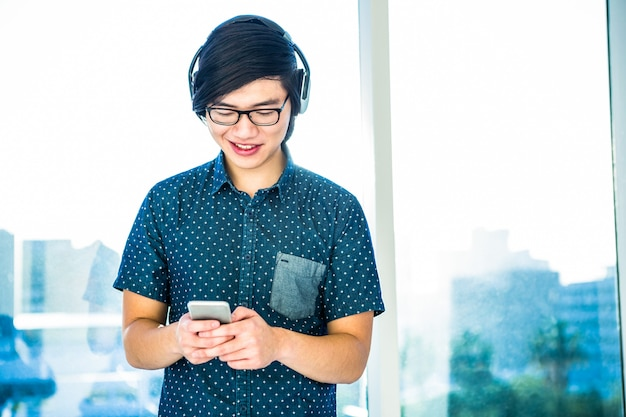 Smiling hipster businessman listening music in his office Premium Photo