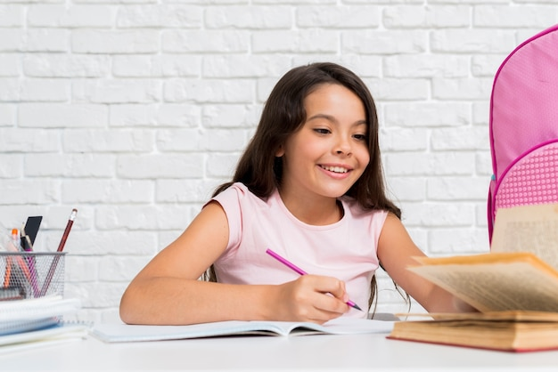 Smiling hispanic girl doing home assignment Free Photo
