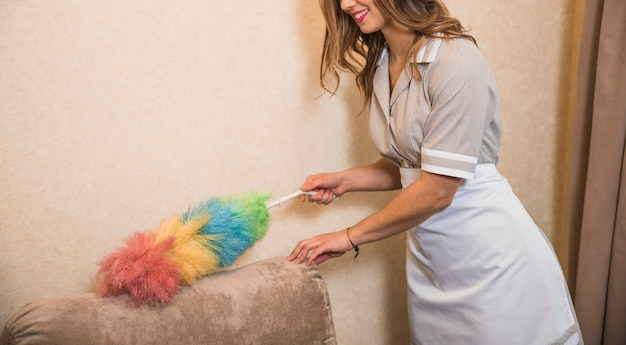 Smiling housekeeper cleaning the sofa with colorful duster Free Photo