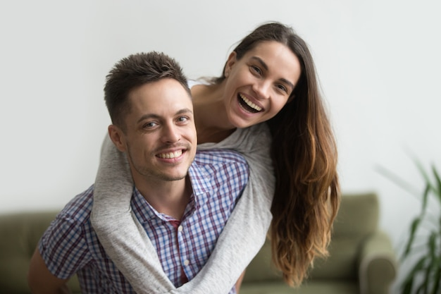 Smiling husband piggybacking cheerful wife at home, happy couple portrait Free Photo
