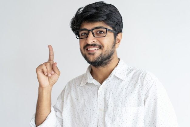 Smiling indian guy pointing upwards and looking at camera Free Photo
