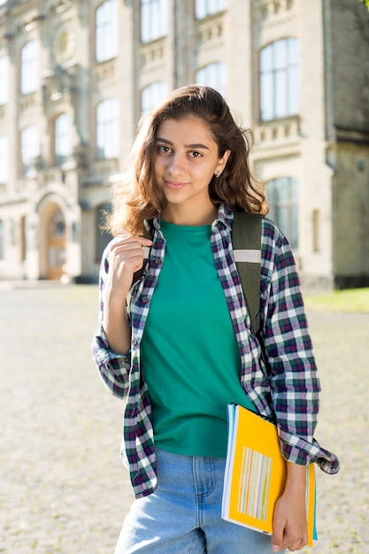 Smiling indian young female student holds educational books standing. happy brunette girl near the university. Premium Photo