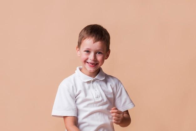 Smiling innocent boy on beige backdrop Free Photo