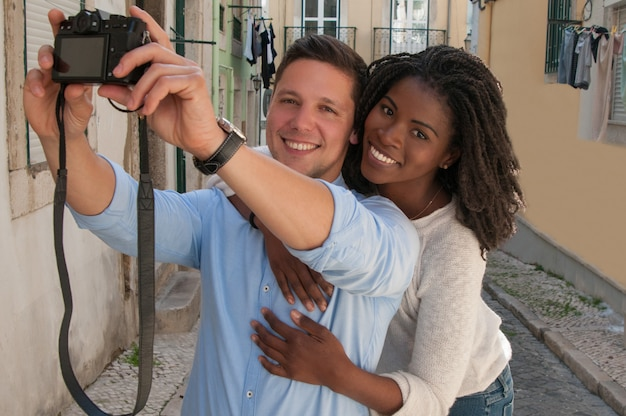 Smiling interracial couple taking selfie photo in street Free Photo