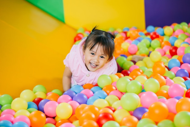 Smiling kid playing in the colorful balls pool. Premium Photo