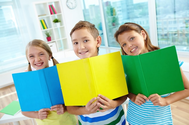 Smiling kids with open books Free Photo