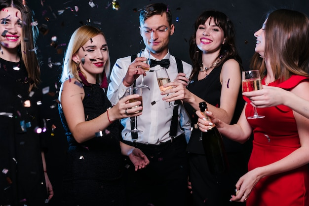 Smiling ladies and guy in evening wear with glasses of drinks between tossing confetti Free Photo