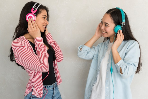 Smiling ladies standing in color headphones and looking at each other Free Photo