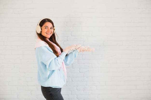 Smiling lady in mittens, earmuffs and scarf with opened hands Free Photo