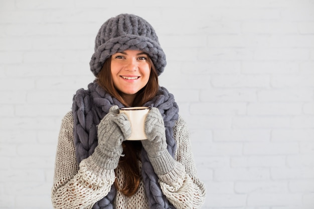 Smiling lady in mittens, hat and scarf with cup in hands Free Photo