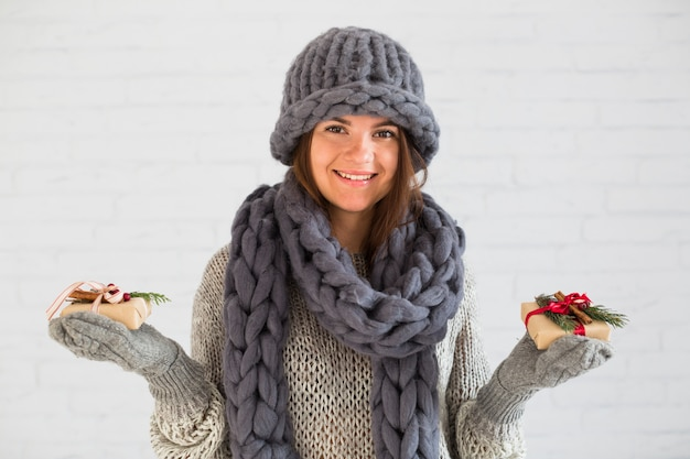 Smiling lady in mittens, hat and scarf with gift boxes Free Photo