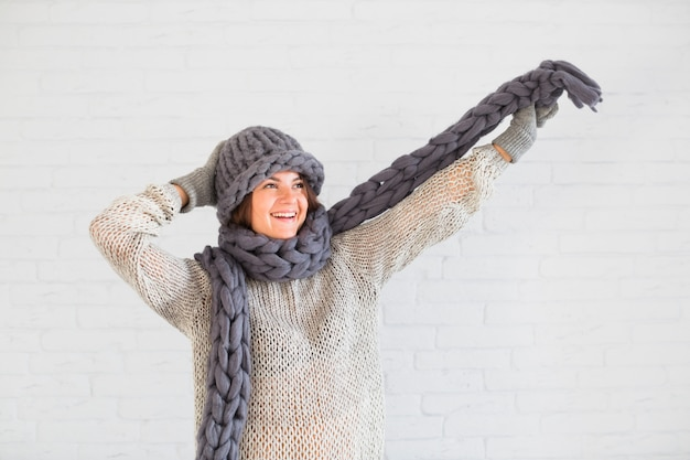 Smiling lady in mittens and hat with scarf in upping hand Free Photo